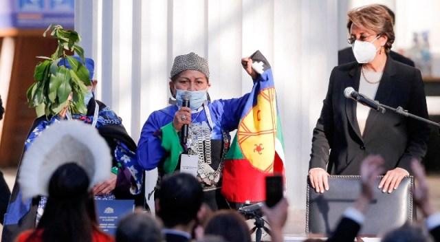 Mujer con barbijo y micrófono, la nueva presidente de la Convención Constitucional, habla al público con un micrófono.