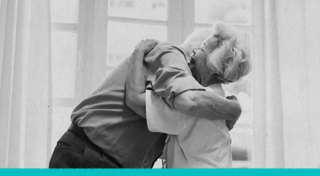 Una pareja mayor se abraza.