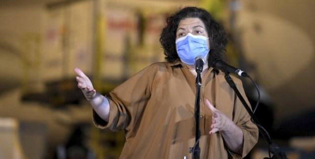 La ministra de Salud, con barbijo, habla de pie frente a un micrófono.