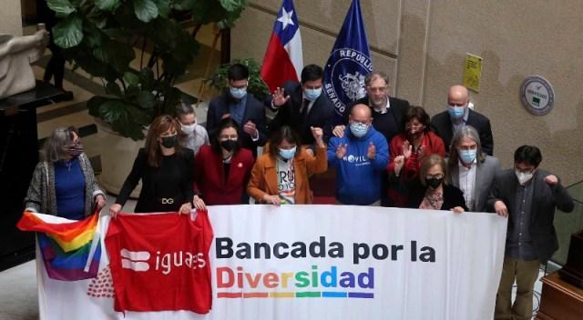 Activistas sostienen una bandera que apoya el matrimonio igualitario.