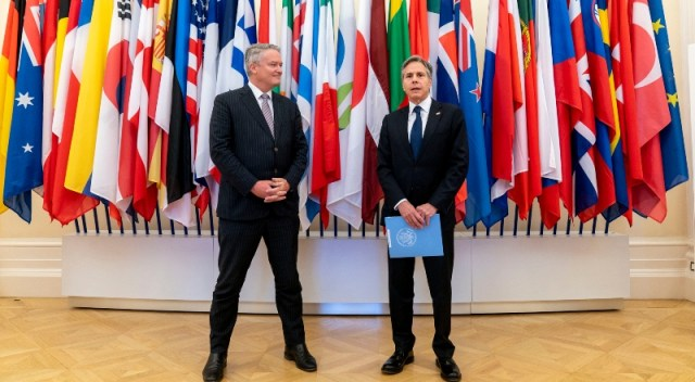 Dos hombres de traje dialogan en una reunión de líderes internacional, con banderas de fondo.