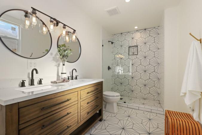 designer bathroom wood cabinetry circle mirrors