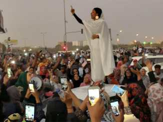 "Alaa Salah leads a crowd of protesters in Sudan with chants of ""Thawra!"" - Revolution!"