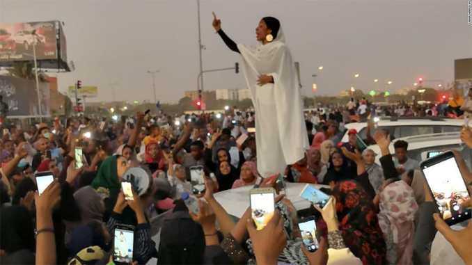 """Alaa Salah leads a crowd of protesters in Sudan with chants of """"Thawra!"""" - Revolution!"""