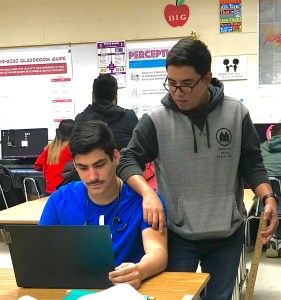 Two Carter students overlook their work on a computer side by side.