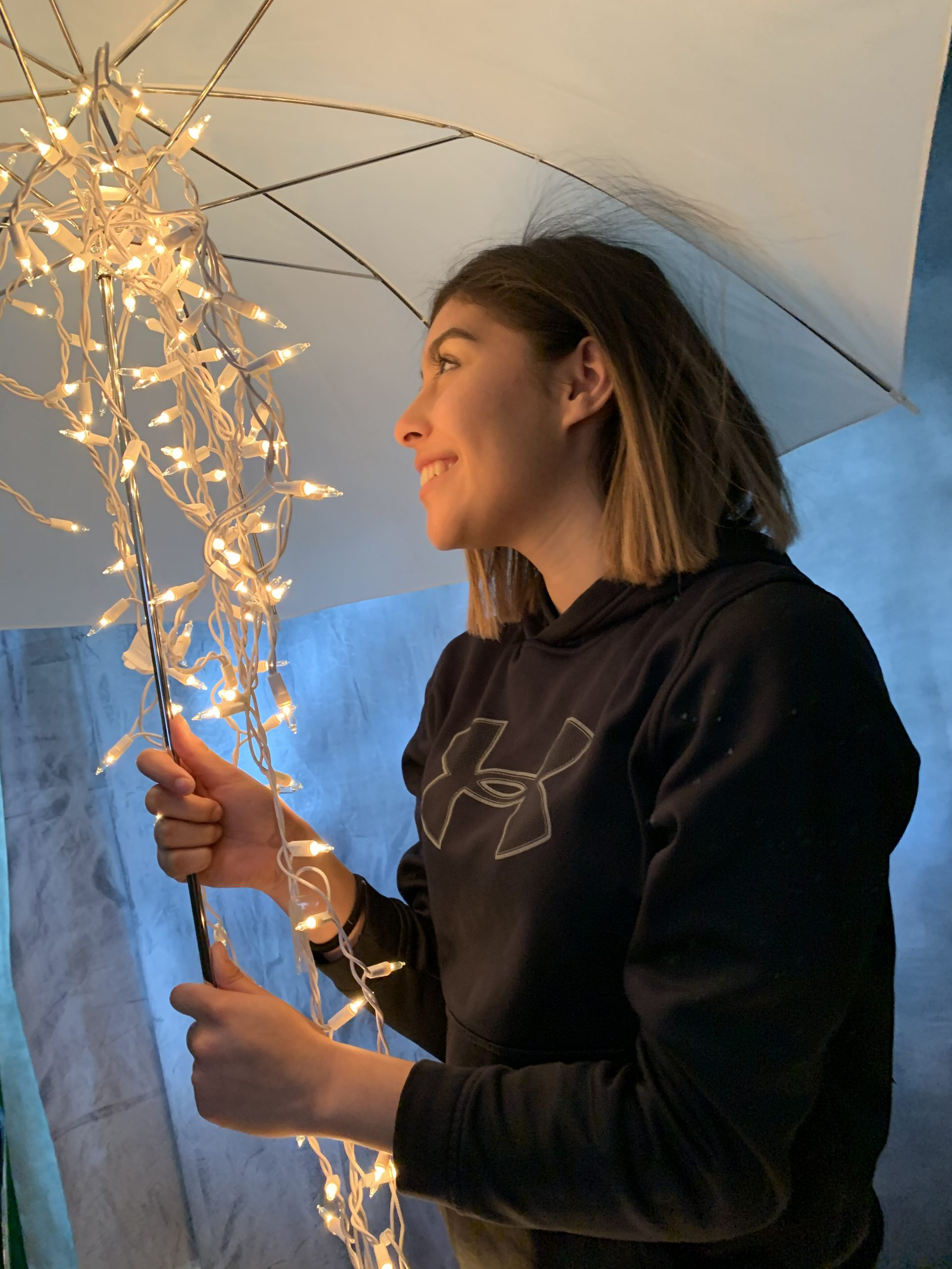 girl holding an umbrella with falling lights