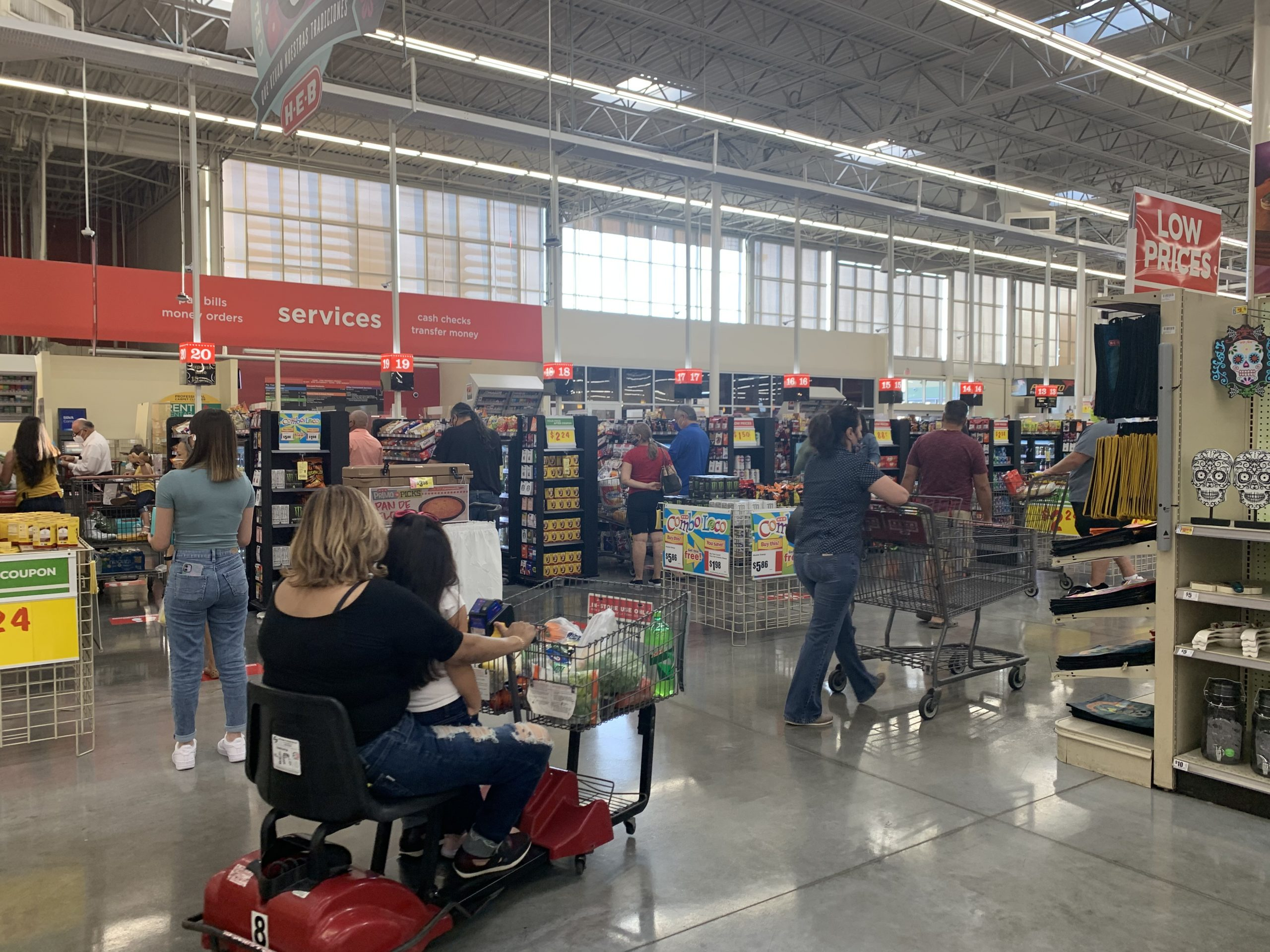 People pushing shopping carts inside of a grocery store