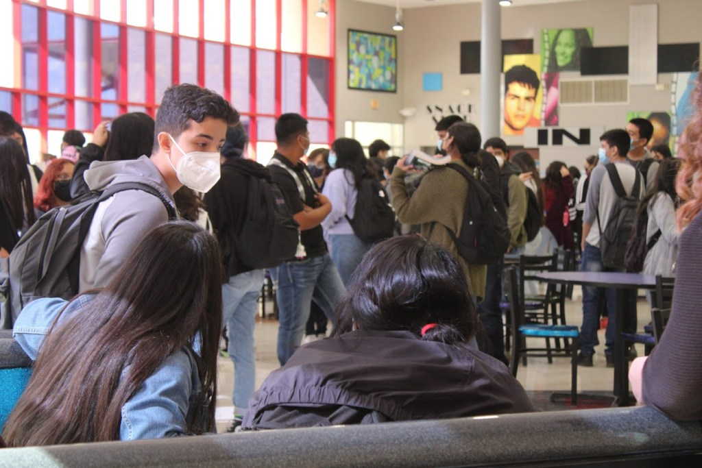 Students talk while waiting for buses.