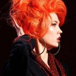 A carrot orange hair color with beehive messy updo