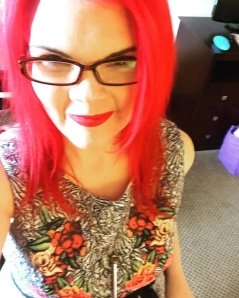 JoEllen taking a selfie with bright red hair, dark glasses, and a black and white dress with flowers on it.