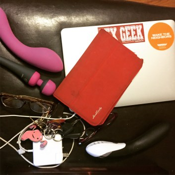 Closed laptop with a sex geek sticker next to two vibrators and keys with a uterus key chain