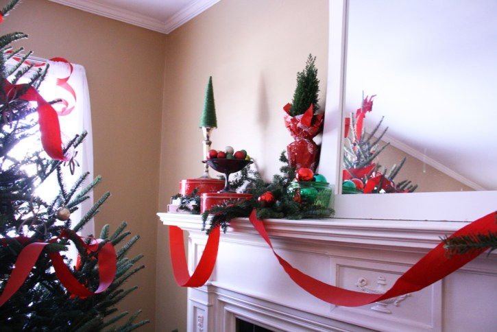 Christmas tree next to fireplace mantle decorated with red ribbon.
