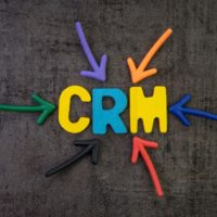 CRM, customer relationship management concept, multi color arrows pointing to the word SSL at the center of black cement chalkboard wall, strategies use to analyze customer interactions and data.