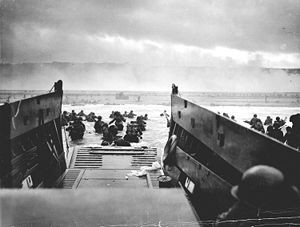 U.S. Army troops wade ashore on Omaha Beach on the morning of 6 June 1944, as the Normandy landings begin.