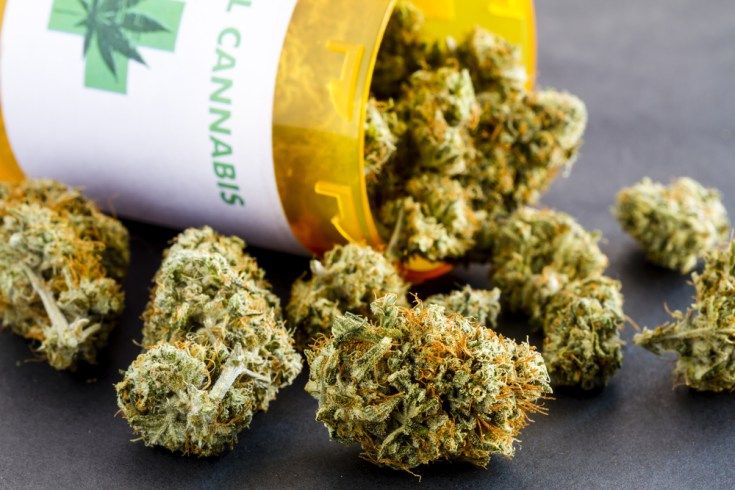 Close up of medical marijuana buds spilling out of prescription bottle with label on black background