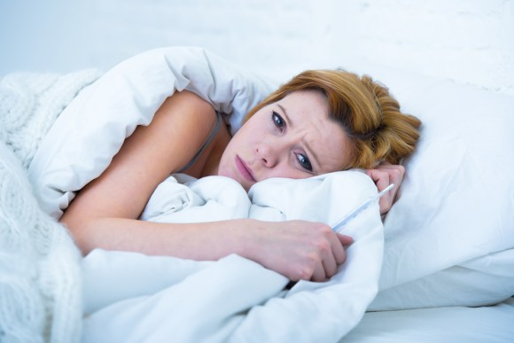 young attractive woman in sad and depressed face expression with eyes wide open lying in bed looking sick and unable to sleep suffering depression , nightmares or insomnia sleeping disorder