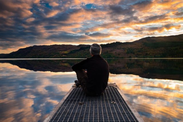 man-reflecting-while-sitting-and-looking-into-the-sky