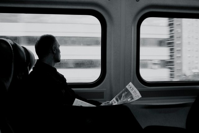 black-and-white-picture-of-man-reading-newspaper-and-looking-out-train-wiindow