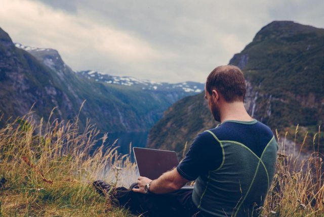 man-with-laptop-on-top-of-mountain