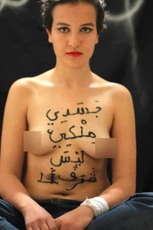 "Topless Tunisian feminist Amina with the phrase ""My body is mine, not somebody's honour"" inscribed across her breasts and stomach in Arabic"