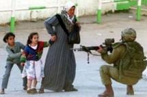 Israeli soldier points gun at woman and children