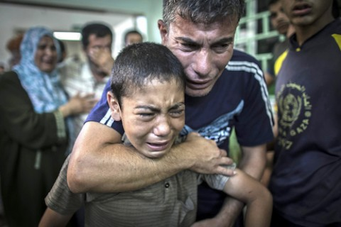 A Palestinian man comforts his son after they lost a relative in the attack on the UN school in the Gaza Strip.