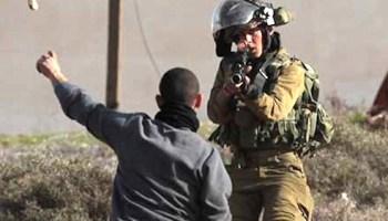 Israeli soldier points gun at child