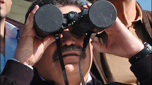Israeli Defence Minister Amir Peretz observing military manoeuvres through binoculars with the lens caps still on