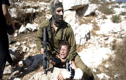 Israeli soldier headlocking Palestinian boy