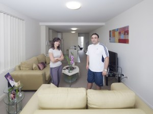 A couple living in one of the cross-over apartments pose for an article in Architecture Australia, discussing how the apartments were occupied, furnished and utilised, following completion.