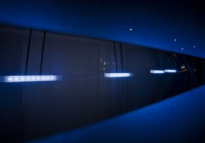 The light pendulums all lit up and viewed through the clear slot in the glass shop frontage.
