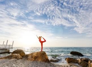 frau-in-roter-sportkleidung-macht-yoga-auf-einem-felsen-am-meer