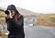 frau-mit-kapuzenjacke-hält-kamera-vors-auge
