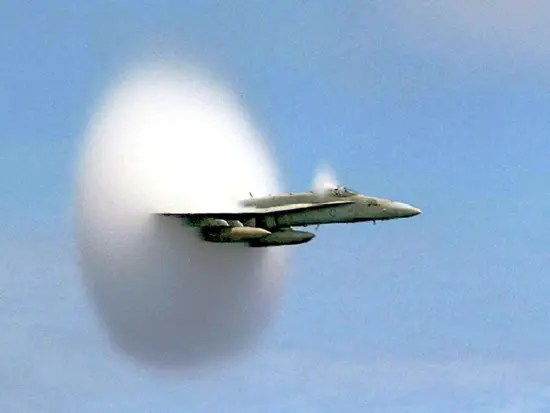 A photograph of the sound barrier being broken by a US Navy Jet as it crosses the Pacific Ocean at the speed of sound just 75 feet above the water. Condensation of water is caused by the rapid expansion and consequent adiabatic cooling of air parcels induced by the shock (expansion/compression) waves caused by the plane outrunning the sound waves in front of it.