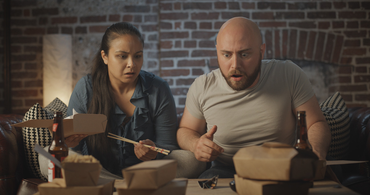 Couple with a take away looking shocked