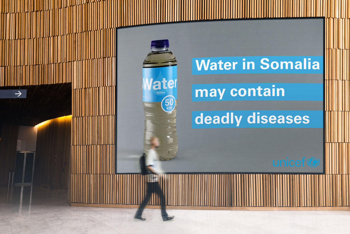 Billboard with a picture of dirty bottled water describing how contaminated water is in Somalia