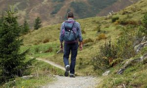 Hiker alone on a trail with backpack on