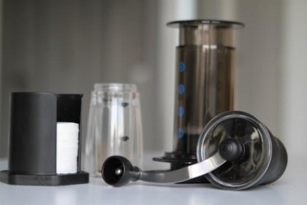 Zum Aeropress Starter Set (Bezug: green cup coffee) zählen eine Handkaffeemühle, Filterpapier und der Aeropress Coffee-Maker.
