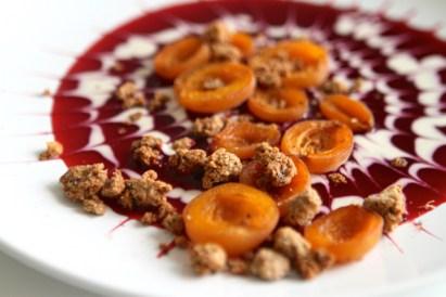 Auf den Fruchspiegel gebackene Aprikosen geben und mit geröstetem Crumble bestreuen.