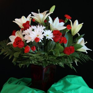 10 Stems of red roses and white lilies, red carnations with chrysanthemums and leather leaves filler.