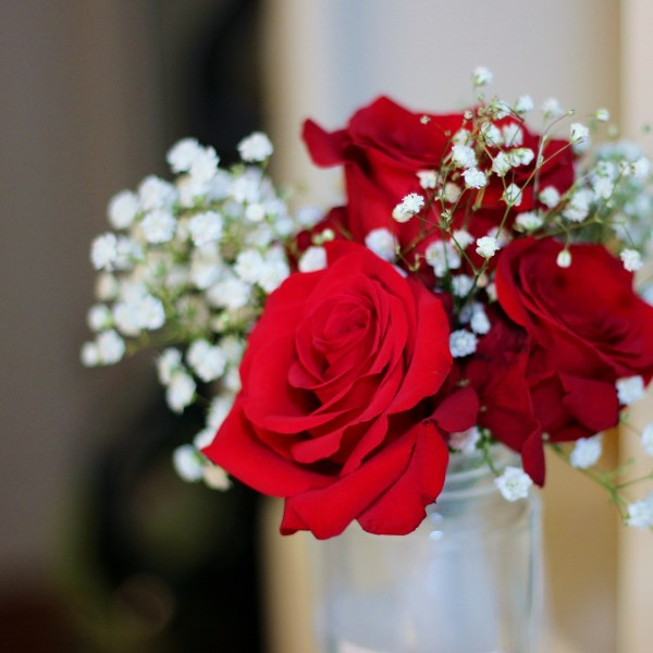 Bridal bouquet of red roses and million star/ baby's breath flowers .