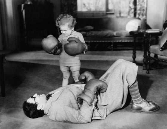 Photo en noir et blanc d'un petit garçon avec des gants de boxe qui a mis KO son père