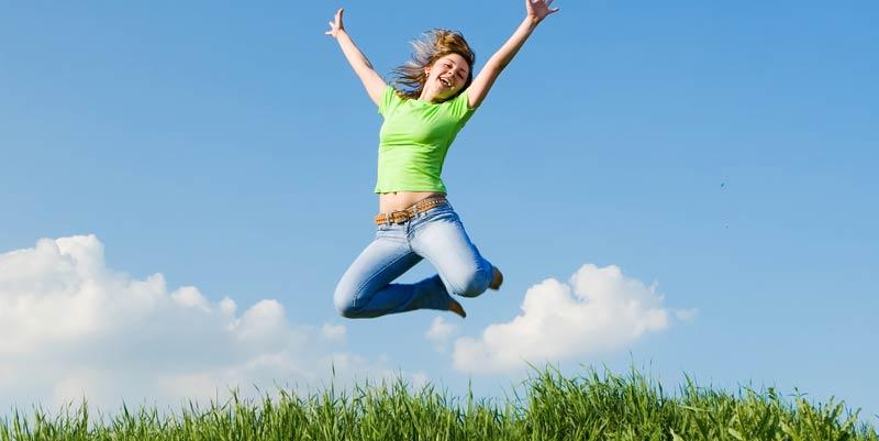 Fille heureuse qui saute en l'air dans la nature