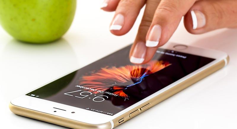 Photographie d'un smartphone et d'une pomme pour illustrer des applications en lien avec l'alimentation