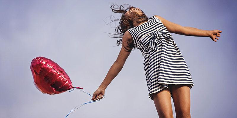 Photographie d'une jeune fille en bonne santé, habillée d'une robe rayée noir et blanche, sautant de joie et tenant dans sa main un ballon de baudruche rouge en forme de cœur, pour illustrer les bénéfices sur la santé d'un régime alimentaire comportant beaucoup d'aliments riches en fibres.