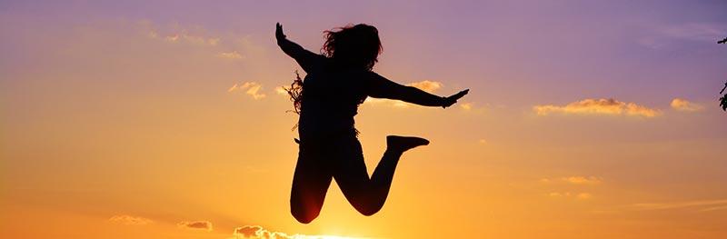 Photographie en couleur d'une femme à contre-jour sautant de joie devant un magnifique couché de soleil coloré