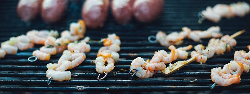 Crevettes et saucisses en train de griller sur un barbecue BBQ pour illustrer les dangers des protéines animales. Les régimes protéinés sont à éviter pour perdre du poids efficacement.