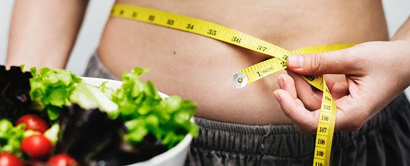 Photographie en gros plan d'une femme avec un peu de graisse abdominale en train de mesurer son tour de taille avec un mètre ruban et tenant une salade dans sa main droite pour perdre du poids