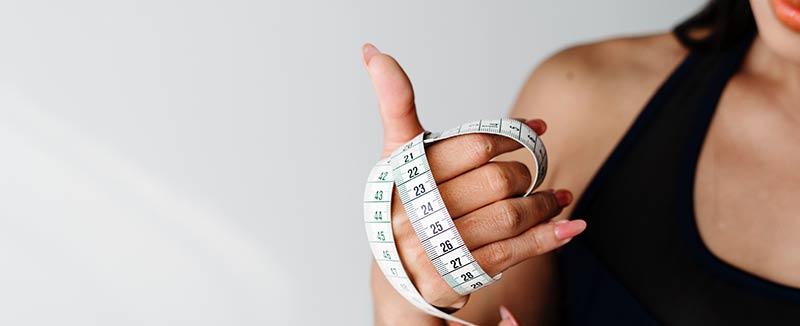 Femme qui tient dans sa main un mètre ruban pour illustrer les dangers de l'obsession de manger sain et de maigrir. Perdre du poids ne doit pas être une obsession.