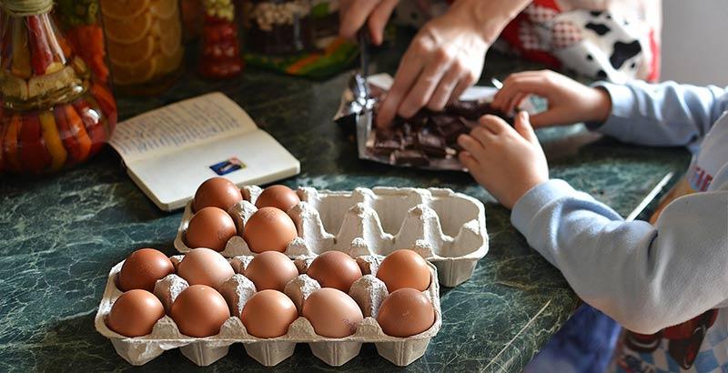 Importance de l'éducation alimentaire : maman en train de cuisiner avec son enfant un gâteau au chocolat. Photogrpahie en gros plan des mains des membres de la famille qui participent à cet atelier cuisine. Des œufs sont posés sur une table en marbre et on aperçois également une tablette de chocolat et un livre de cuisine ouvert.